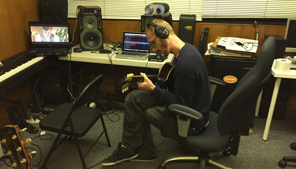 Mitchell Thomas in studio with guitar